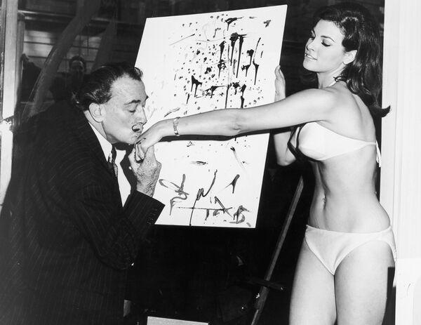 Сальвадор Дали целует руку американской актрисе Ракель Уэлч у её абстрактного портрета