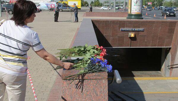 Женщина возлагает цветы у пешеходного перехода станции метро Парк победы, архивное фото