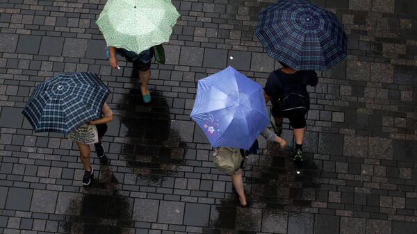 Люди с зонтами на улице Пекина