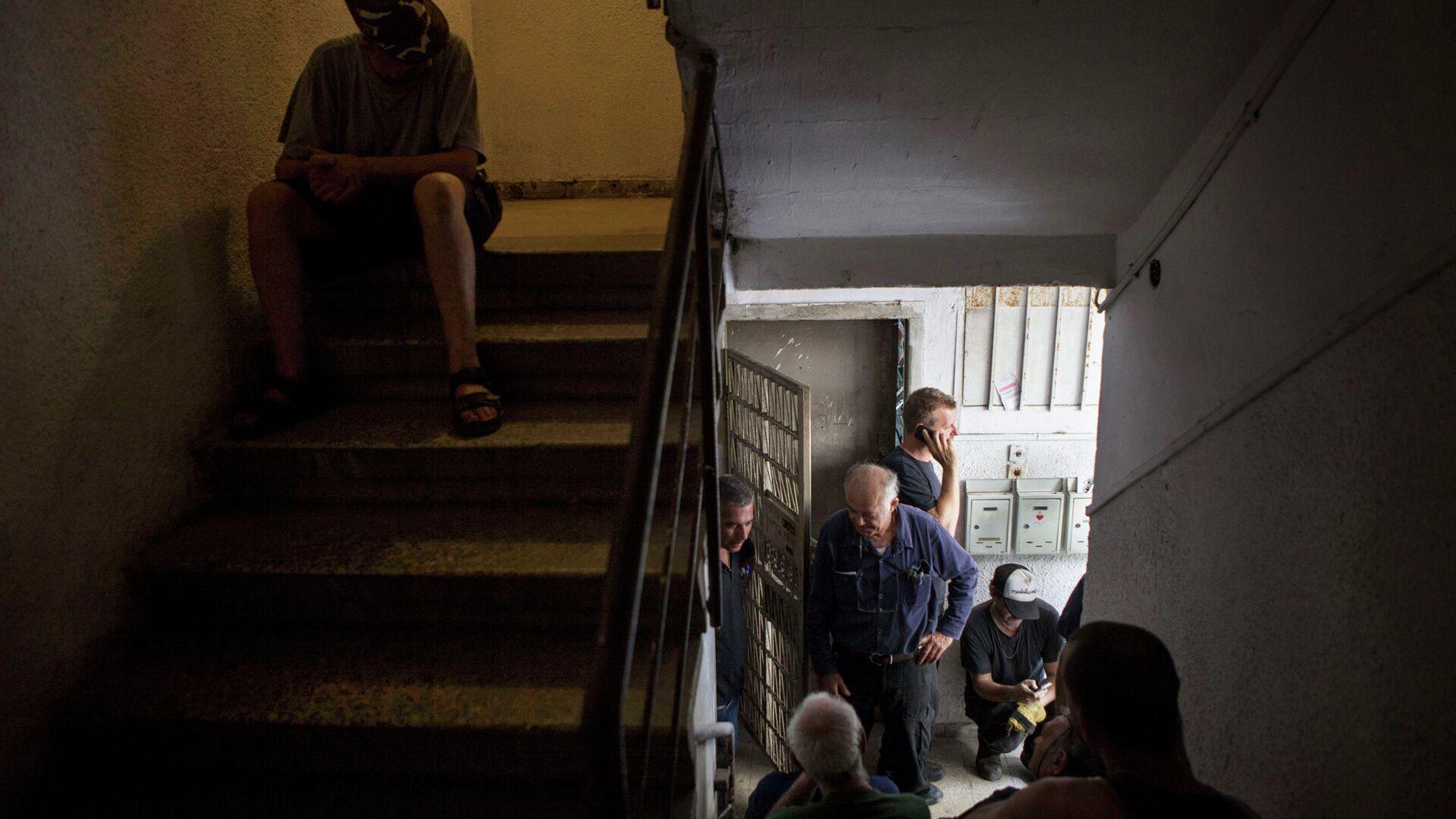 Жители города Тель-Авив укрываются в здании во время ракетного обстрела - РИА Новости, 1920, 12.05.2021