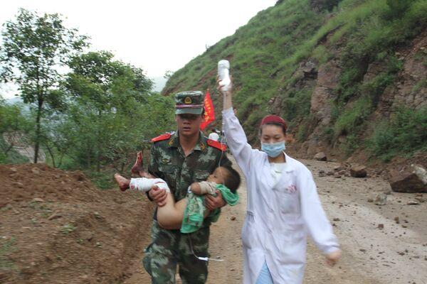 Военный и медсестра несут раненого в результате землетрясения ребенка