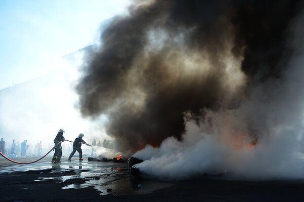 Пожарные тушат подожженные активистами покрышки на площади Независимости в Киеве