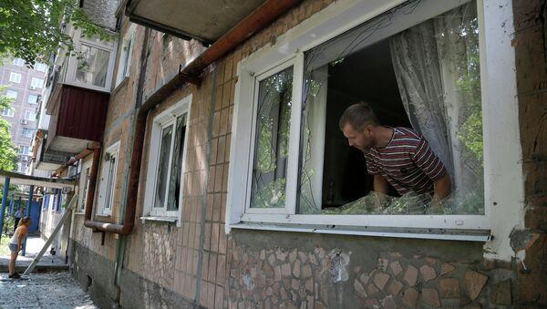 Местный житель осматривают повреждения после обстрела жилого дома в Донецке. Архивное фото