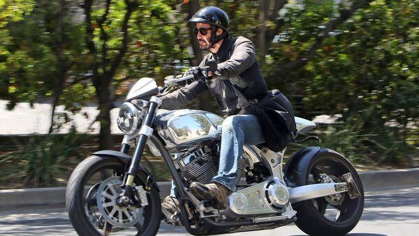Каину Ривз едет на своем мотоцикле по Беверли Хиллс