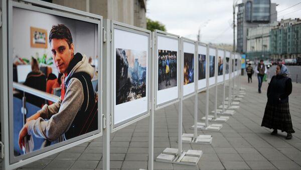 Жительница Москвы рассматривает работы погибшего на Украине фотокорреспондента Андрея Стенина у здания МИА Россия сегодня
