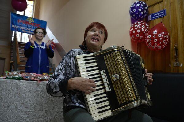 Женщина играет на аккордеоне на избирательном участке в Первомайском районе Новосибирска