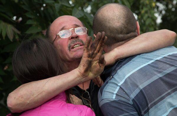 Мужчина обнимает своих родственников после обстрела в Донецке