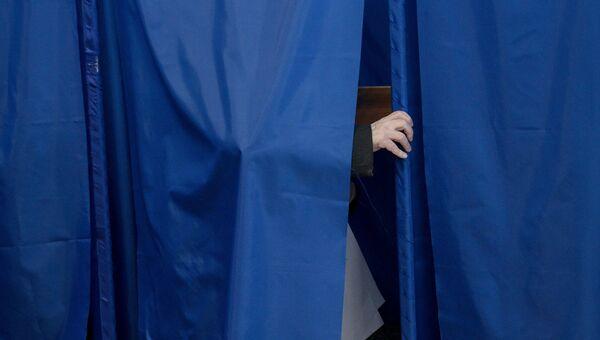 Избиратель в кабинке для голосования на досрочных выборах депутатов парламента Украины