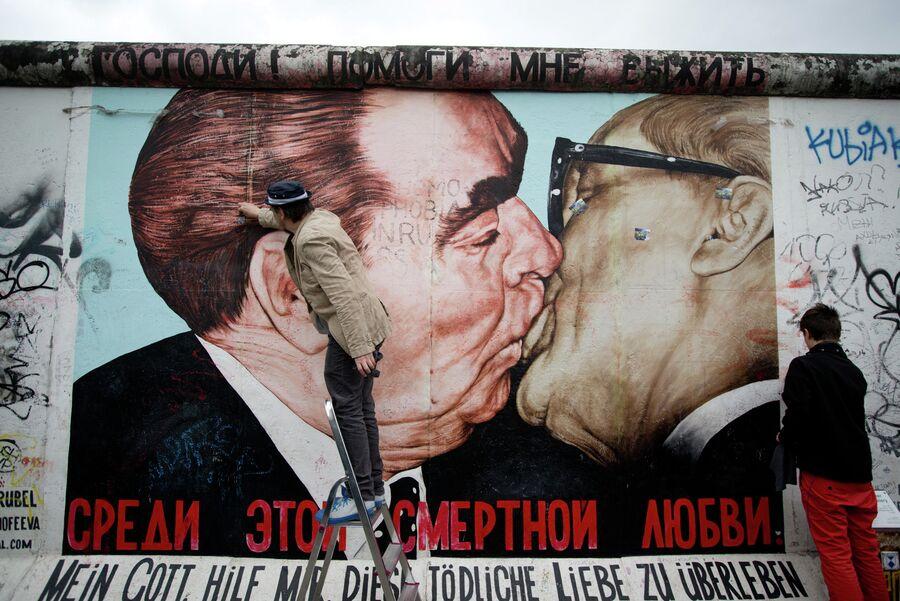 Художник Дмитрий Врубель с сыном очищают граффити расположенное на Берлинской стене