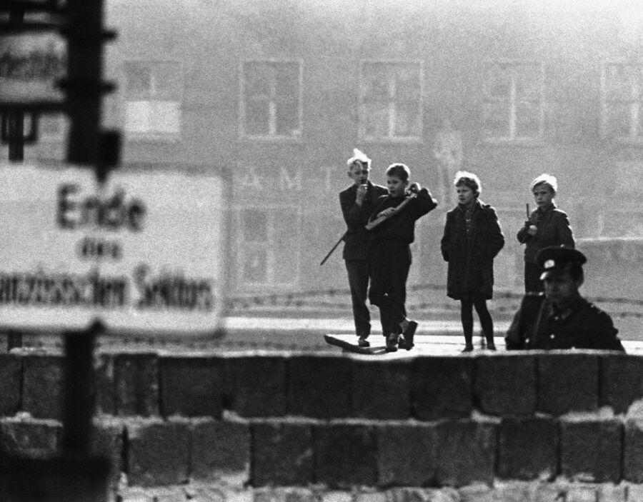 Подростки из Восточного Берлина идут вдоль Берлинской стены с игрушечным оружием