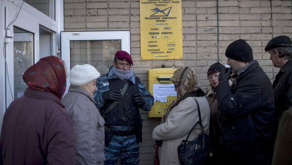 Местные жители в очереди на получение пенсий и компенсаций в городе Луганске