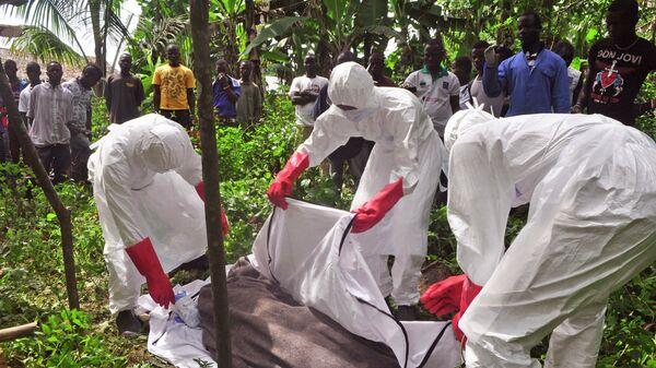 Сотрудники крематория эвакуируют тело человека, предположительно погибшего от вируса Эболы в Либерии. Архивное фото