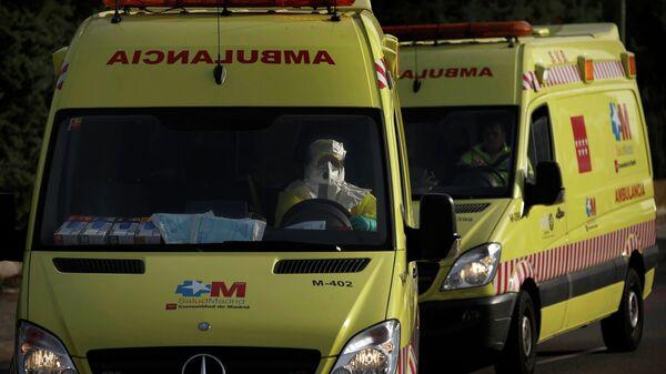 Водитель скорой помощи в защитном костюме везет пациента в больницу в Мадриде