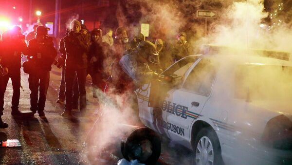 Сотрудник полиции стоит возле автомобиля, в который протестующие кинули дымовую шашку