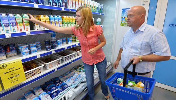 Покупатели у полки с молочной продукцией в магазине. Архивное фото