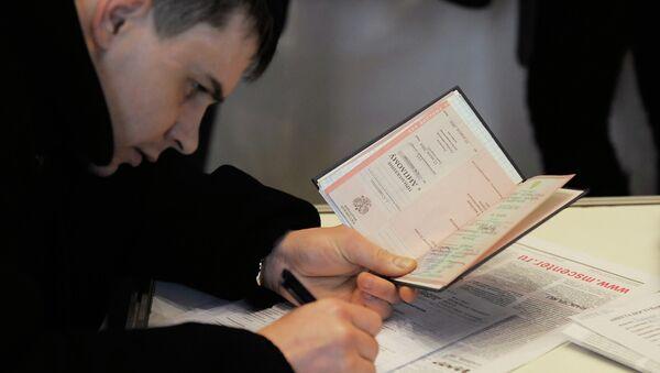 Соискатель заполняет анкету и держит в руках диплом. Архивное фото