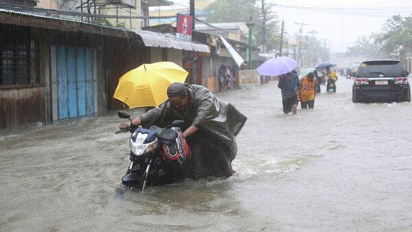 Люди на затопленной улице во время тайфуна Хагупит на Филиппинах