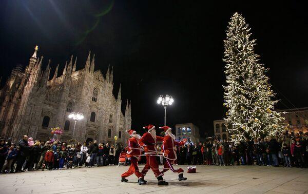 Мужчины в костюмах Санта-Клаусов перед готическим собором Дуомо в Милане, Италия