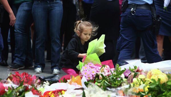 Люди несут цветы в память о погибших в кафе в Сиднее, Австралия