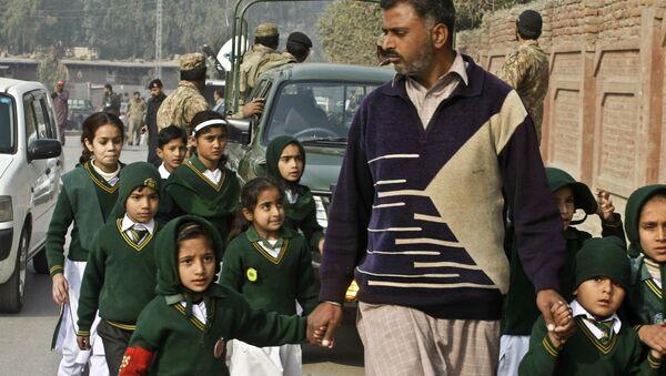 Школьники неподалеку от военного училища в Пакистане, захваченного боевиками