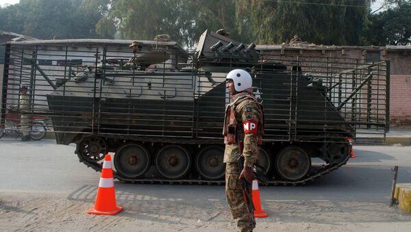 Пакистанские силы безопасности неподалеку от военного училища в Пакистане, захваченного боевиками