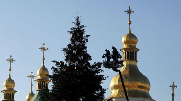 Работники украшают новогоднюю елку перед Софийским собором в центре Киева,