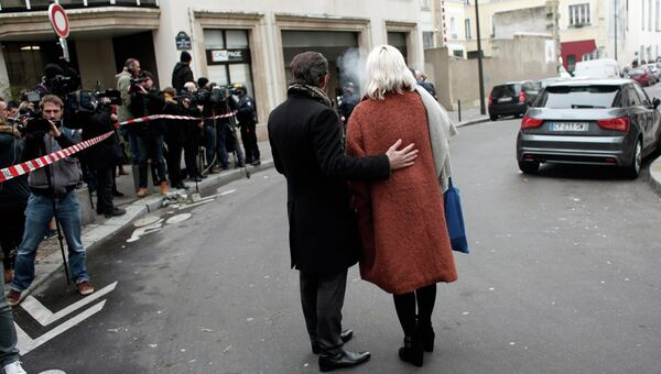 Люди стоят возле офиса издания Charlie Hebdo в Париже