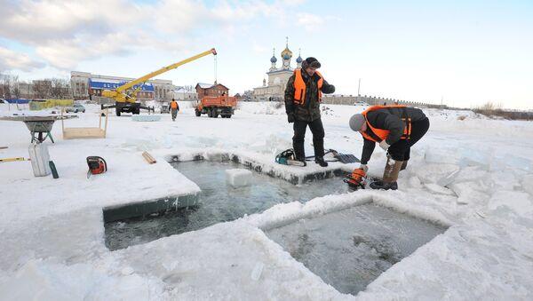 Рабочие подготавливают купель к празднику Крещения на озере Смолино
