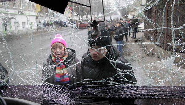 Люди смотрят через лобовое стекло обстрелянного троллейбуса в Донецке