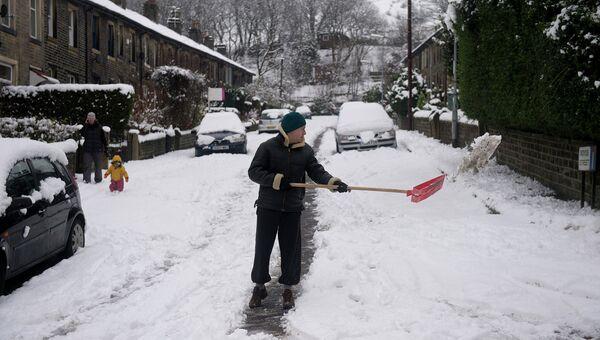 Человек очищает улицу от снега в деревне Марсден
