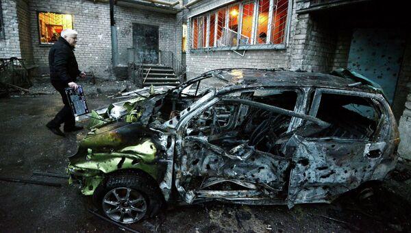 Сгоревшая автомашина у пострадавшего от обстрела жилого многоэтажного дома в Донецке