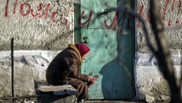 Жительница Дебальцево сидит возле поврежденного дома. Архивное фото