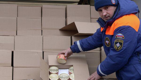 Сотрудник МЧС России демонстрирует банки с тушеной говядиной - гуманитарный груз одного из грузовых автомбилей шестнадцатого российского гуманитарного конвоя. Архивное фото