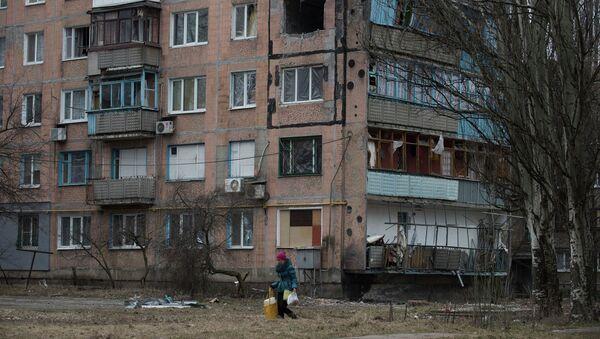 Женщина проходит мимо разрушенного жилого дома в Авдеевке. Архивное фото