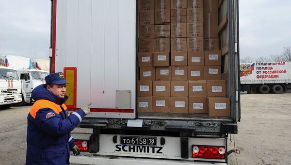 Сотрудник МЧС РФ демонстрирует содержимое груза с гуманитарной помощью