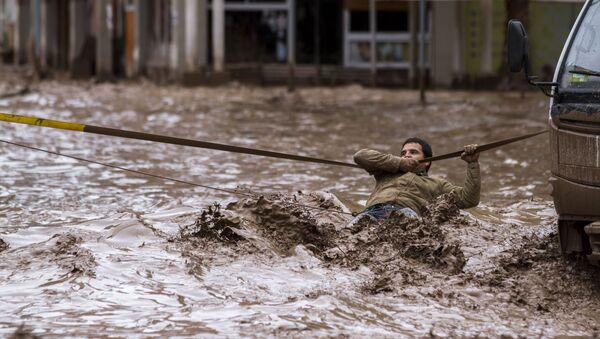 Мужчина пытается пересечь улицу в городе Копьяпо во время наводнения в Чили. 26 марта 2015