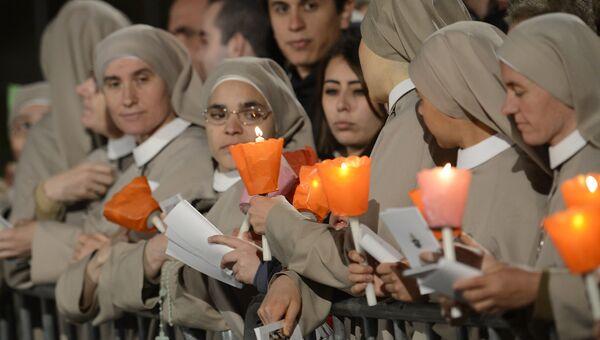 Монахини держат свечи во время празднования Крестного пути в Страстную пятницу в Риме. Архивное фото