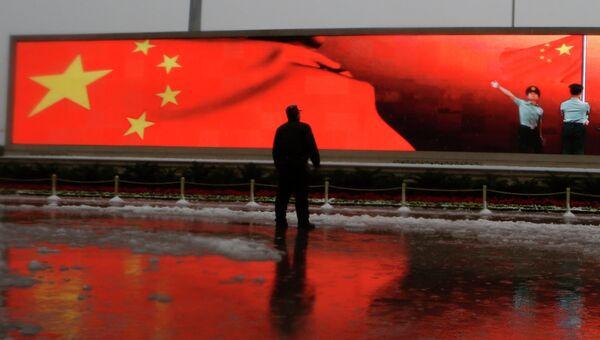 Человек на фоне экрана с флагом Китая, Пекин. Архивное фото