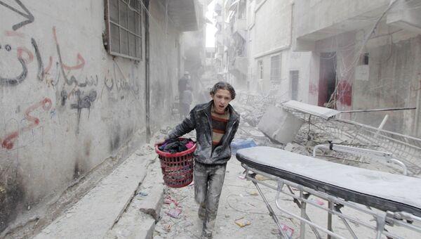 Сирийский подросток в одном из районов Алеппо, пострадавших от бомбардировки