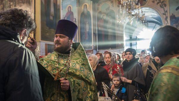 Священнослужитель и прихожане во время службы в канун празднования Входа Господня в Иерусалим в храме в честь Воздвижения Честного и Животворящего Креста Господня в Омске