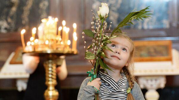 Девочка перед патриаршим служением в канун празднования Входа Господня в Иерусалим в Храме Христа Спасителя в Москве. Архивное фото