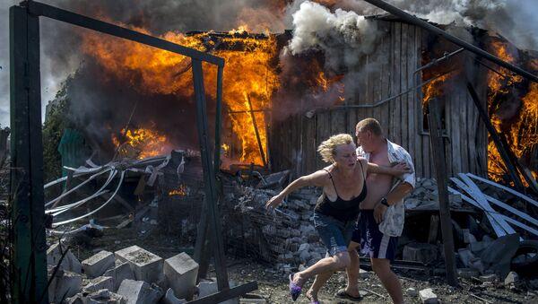 Местные жители спасаются от пожара, возникшего в результате авиационного удара вооруженных сил Украины по станице Луганская, 2 июля 2014