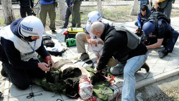 Сотрудники миссии ОБСЕ оказывают первую помощь репортеру телеканала Звезда Андрею Луневу. Архивное фото