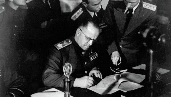 Маршал Советского Союза Георгий Константинович Жуков (в центре) подписывает Акт о безоговорочной капитуляции фашистской Германии в Карлсхорсте в Берлине. Архив