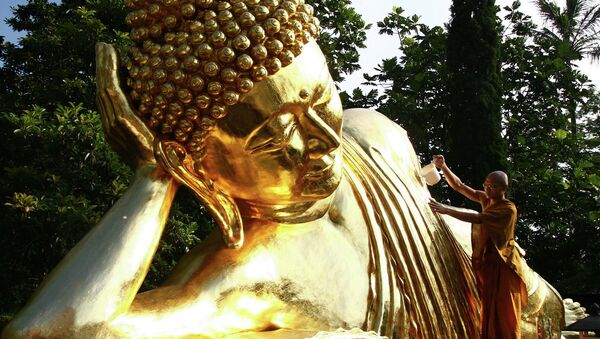 Монах у статуи Будды в храме