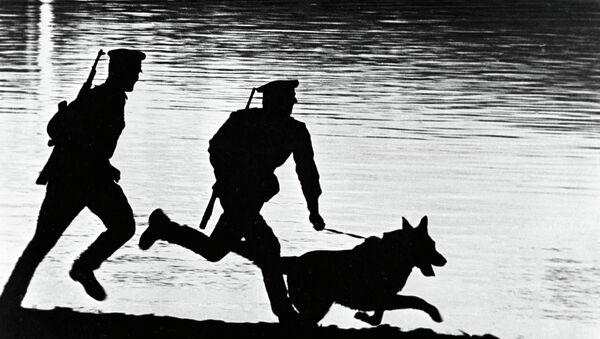 Пограничники с собакой бегут по берегу реки. Архивное фото