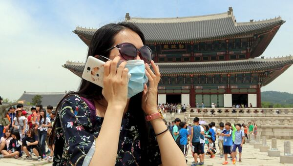 Женщина в защитной маске возле дворца Кёнбоккун в Сеуле во время вспышки вируса MERS в Южной Корее