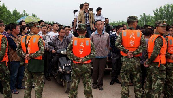 Сотрудники китайской военизированной полиции охраняют место проведения спасательных работ у реки Янцзы
