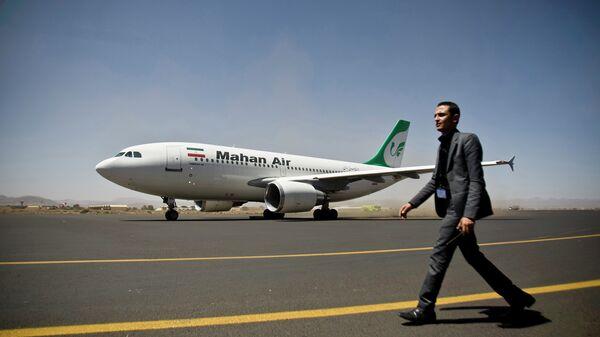Сотрудник службы безопасности аэропорта рядом с самолетом иранской авиакомпании Mahan Air. Архивное фото