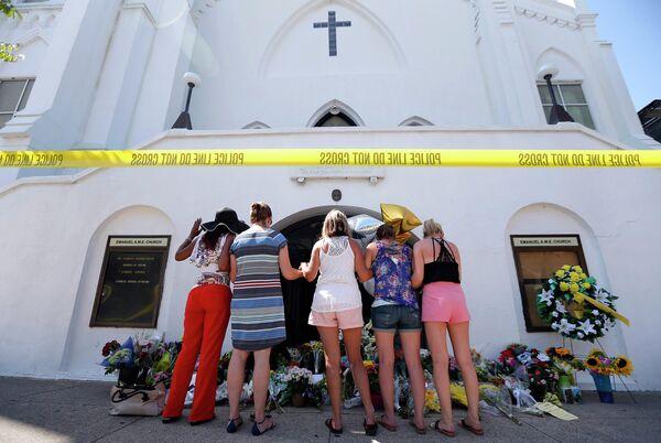 Люди, пришедшие почтить память погибших во время стрельбы в африканской методистской епископальной церкви Эмануэль города Чарлстон, США